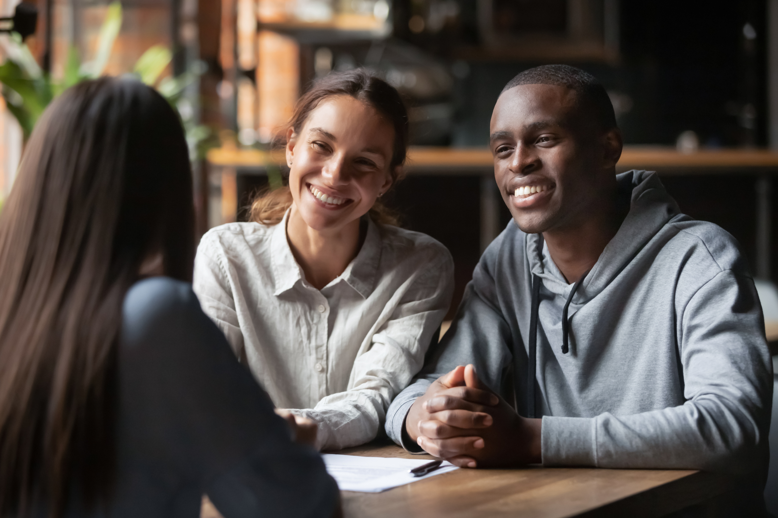 Smiling diverse couple listening to a realtor
